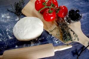 Zubereitung des Focaccia mit schwarzen Oliven, Tomaten und Knoblauch